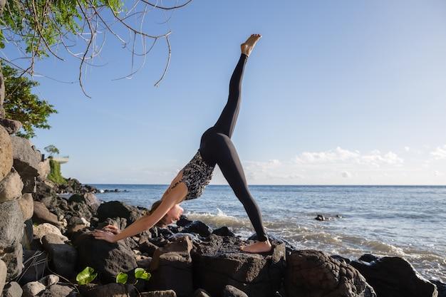 Mujer haciendo yoga en la playa de roca tres