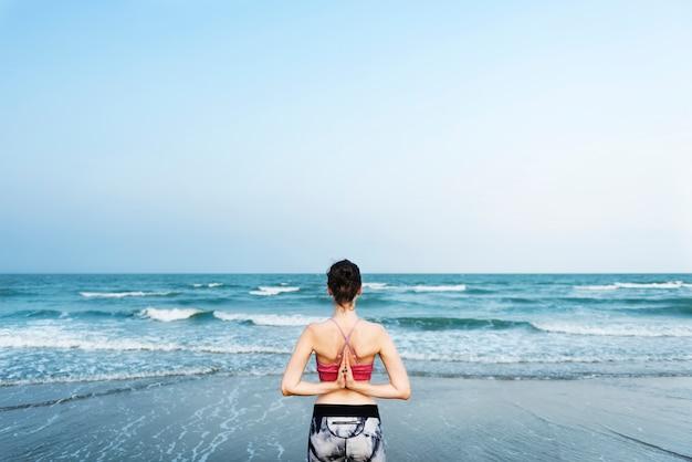 Una mujer está haciendo yoga en la playa.