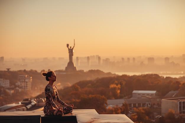 Mujer haciendo yoga en el techo de un rascacielos en la gran ciudad.