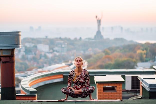 Mujer haciendo yoga en el techo de un rascacielos en la gran ciudad