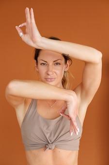 Mujer haciendo yoga con un top beige sobre un fondo naranja