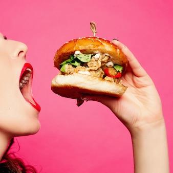 Mujer hambrienta con la boca abierta comiendo hamburguesa grande.