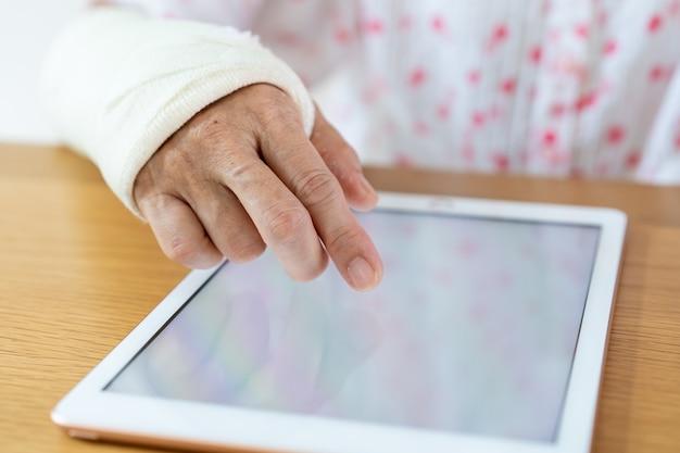 Mujer herida del brazo que lee un libro electrónico en el cierre de la tableta para arriba. salud y bienestar en el concepto de sociedad de envejecimiento.