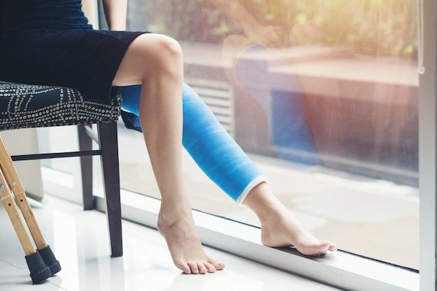 Mujer herida con férula de pierna sentada y muletas de madera en el hospital