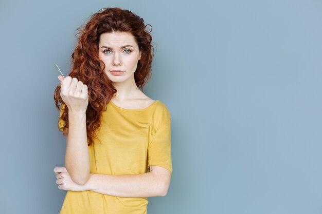Mujer hermosa. agradable agradable mujer de pelo rojo de pie contra un fondo gris y mirándote mientras sostiene una tarjeta