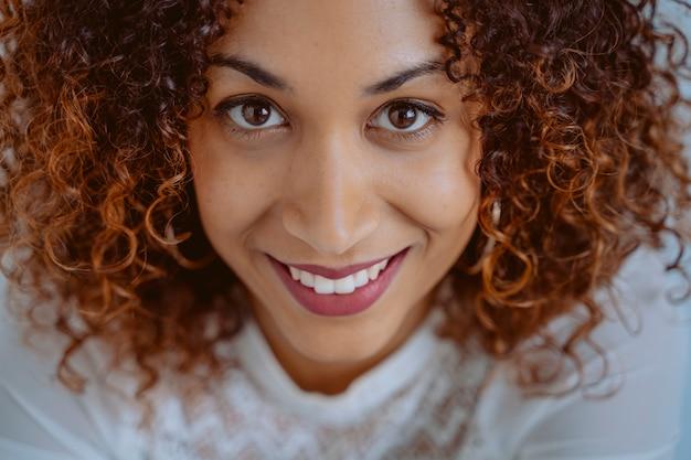 Mujer hermosa aislada con sonrisa perfecta. mujer alegre con dientes blancos dentista. retrato de mujer joven afroamericana con piel suave perfecta. concepto de belleza y cuidado de la piel. estilo de vida afro.