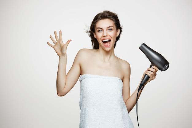 Mujer hermosa alegre en toalla sonriendo riendo cantando con secador de pelo haciendo cara divertida. spa de belleza y cosmetología.