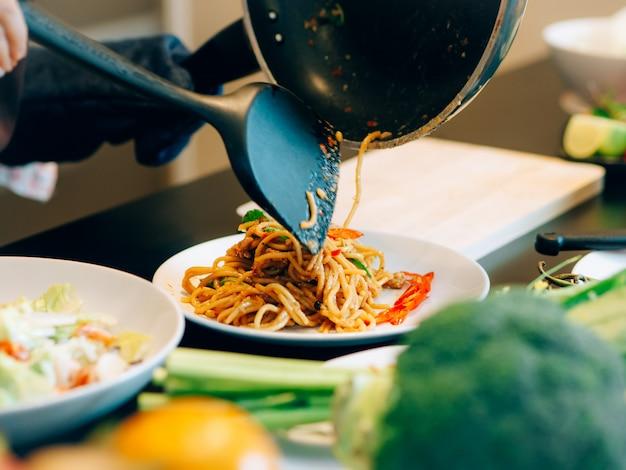 La mujer hermosa asiática durante hace la comida de los espaguetis en la cocina