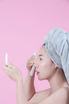 La mujer hermosa asiática limpia la cara en un fondo rosado.