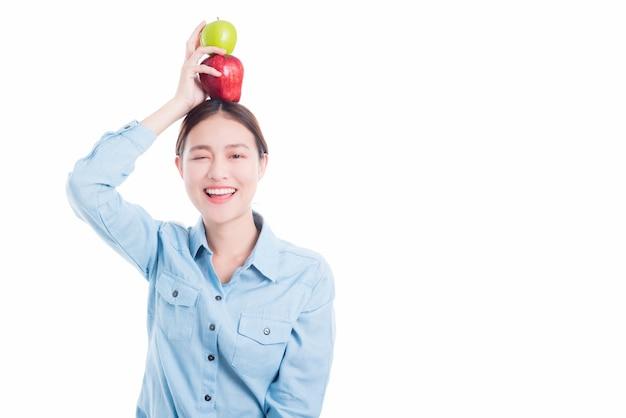 La mujer hermosa asiática puso manzanas en la cabeza y sonríe sobre el fondo blanco
