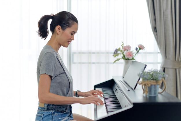 Mujer hermosa asiática que juega el piano electrónico en casa.