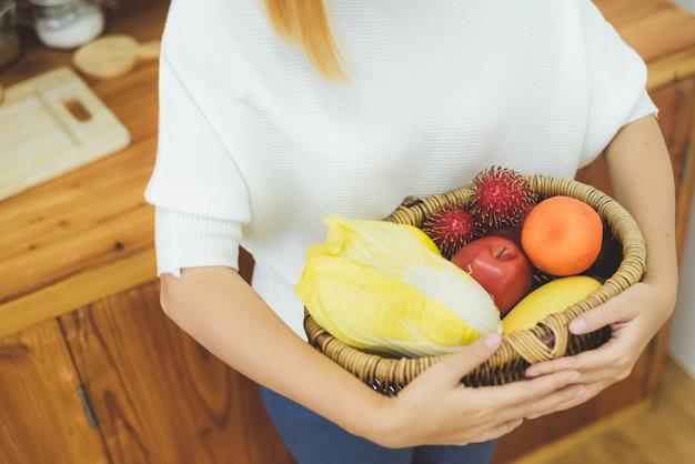Mujer hermosa asiática que sostiene la fruta y verdura en la cocina en su hogar