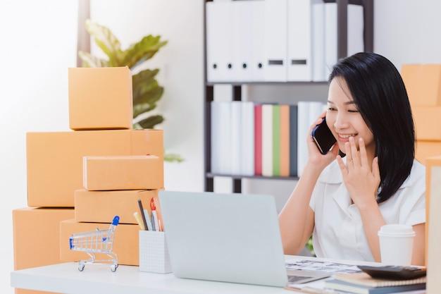 Mujer hermosa asiática que trabaja con la tienda de negocios en línea en casa. la empresaria propietaria comienza con aceptar pedidos.