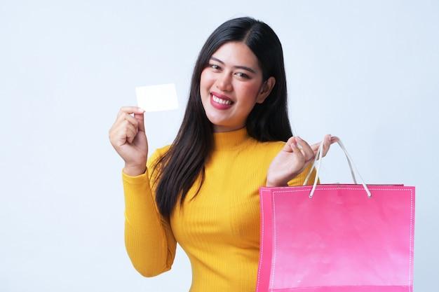 Mujer hermosa asiática con la tarjeta de crédito y el bolso shoping en el fondo blanco