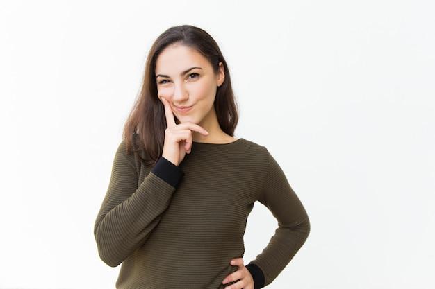 Mujer hermosa astuta pensativa que toca la barbilla