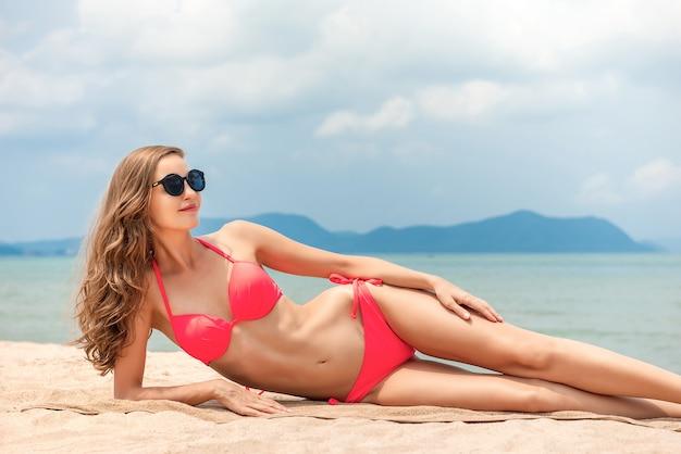Mujer hermosa atractiva en el bikini rosado que miente en la playa en verano