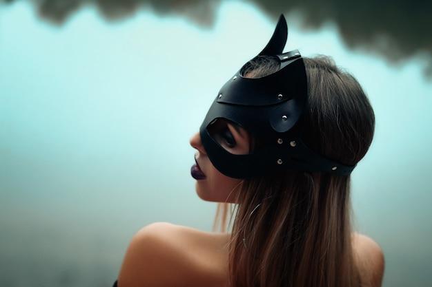 Mujer hermosa atractiva en máscara del gato negro.