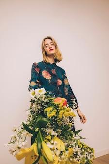 Mujer hermosa atractiva en el vestido que muestra el ramo de flores frescas