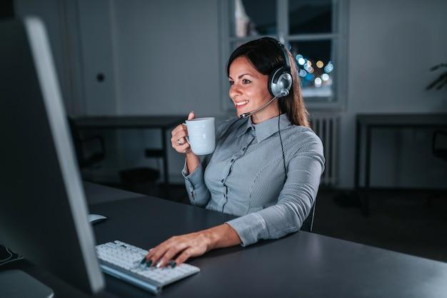 Mujer hermosa con las auriculares y una taza que trabaja en la noche.