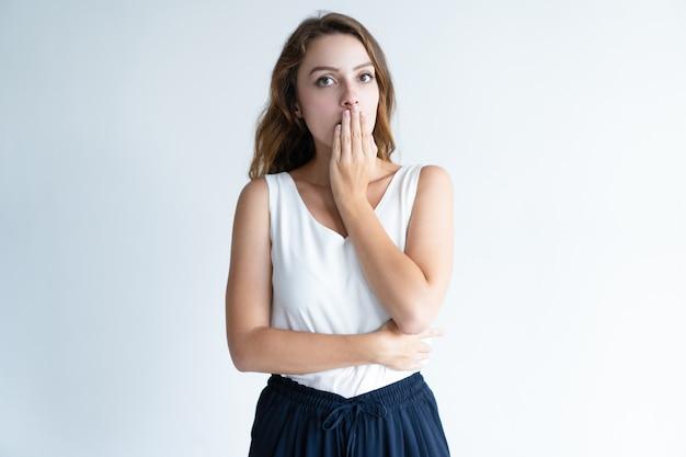 Mujer hermosa avergonzada que cubre la boca con la mano