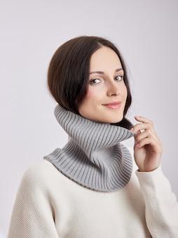 Mujer hermosa en una bufanda de redecilla sobre un fondo blanco. otoño ropa de abrigo