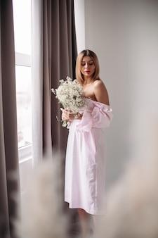 Mujer hermosa con cabello rubio medio mirando su boquet de flores blancas