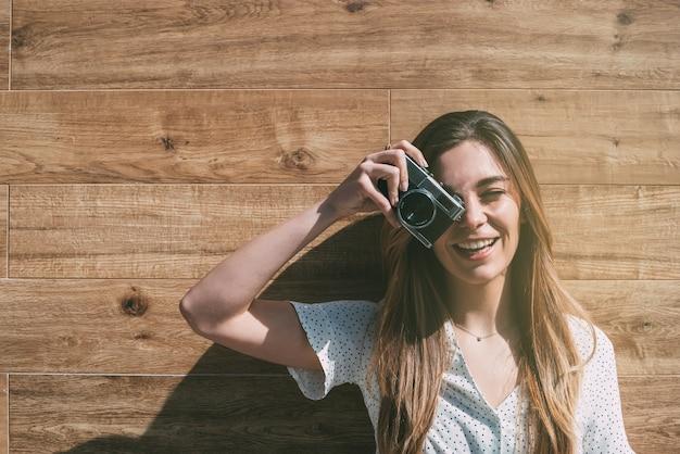 Mujer hermosa con la cámara vieja de la vendimia que toma la foto