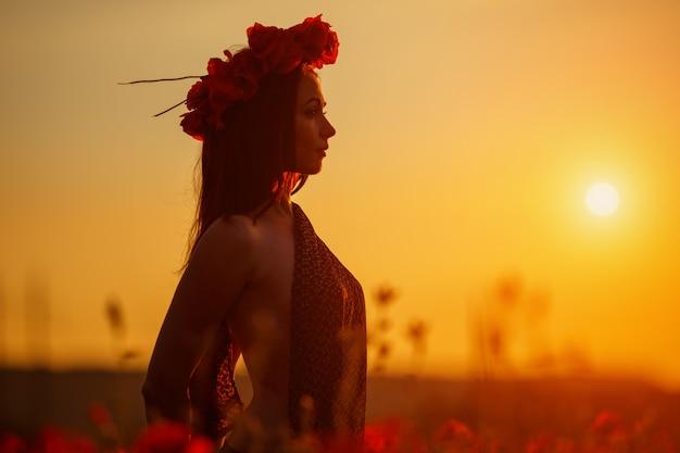 Mujer hermosa en el campo de amapolas al atardecer Foto Premium