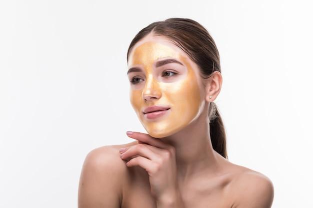 Mujer hermosa con la cara del tacto cosmético de la piel de oro aislada en la pared blanca. belleza cuidado de la piel y tratamiento
