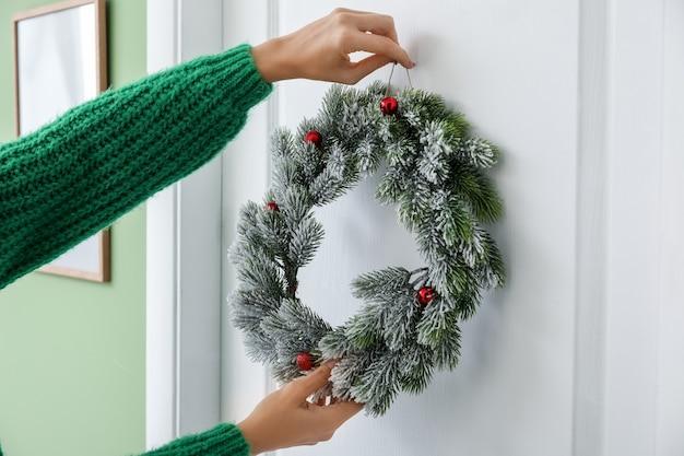 Mujer hermosa corona de navidad colgando en la puerta
