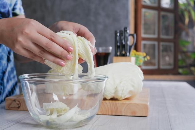 Una mujer hermosa está cortando verduras en la cocina en casa.