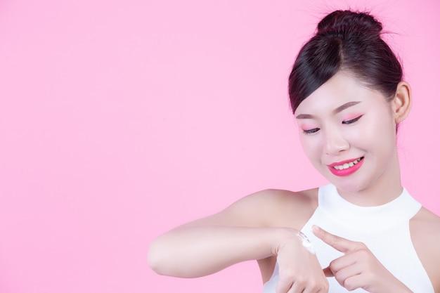Mujer hermosa con crema en la piel en un fondo rosado.