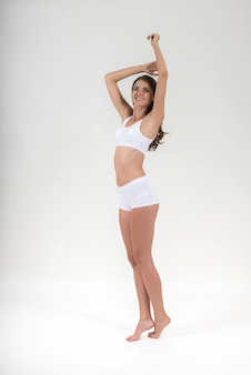 Mujer hermosa con el cuerpo sano en el fondo blanco