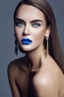 Mujer hermosa dama con labios azules y joyas
