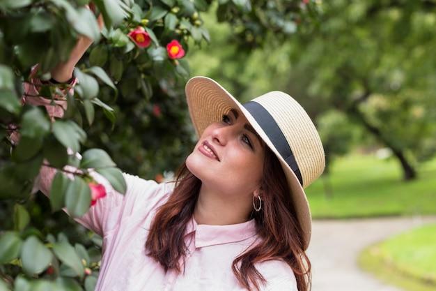 Mujer hermosa debajo del árbol floreciente en parque