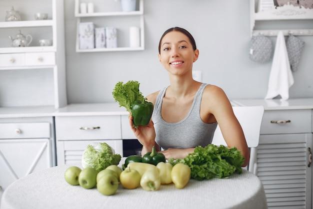 Mujer hermosa y deportiva en una cocina con verduras