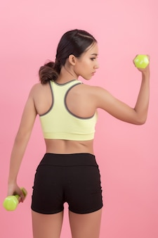 Mujer hermosa deportiva que ejercita con pesa de gimnasia