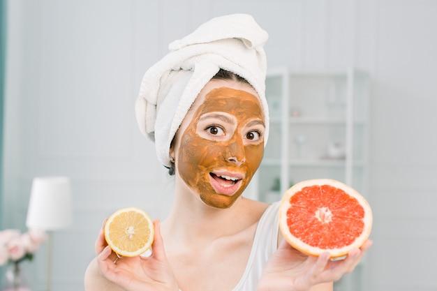 Mujer hermosa divertida con rodajas de limón y pomelo. foto de niña en una toalla blanca con máscara facial de barro marrón, con procedimientos de spa.