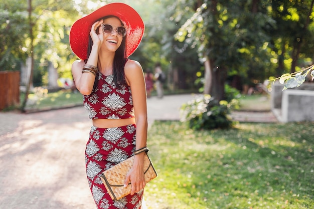 Mujer hermosa elegante caminando en el parque en traje tropical. dama en tendencia de moda de verano estilo callejero con bolso de paja, sombrero rojo, gafas de sol, accesorios. niña sonriendo feliz de vacaciones.