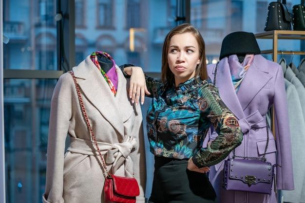 Una mujer hermosa elige un abrigo en la tienda.