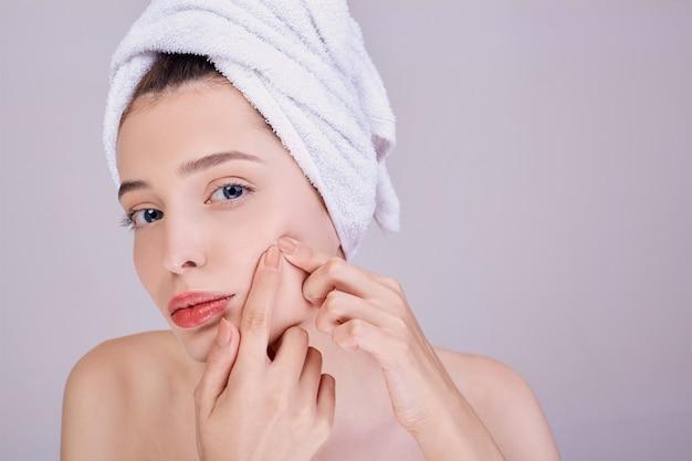 Una mujer hermosa elimina imperfecciones de la piel de la cara.