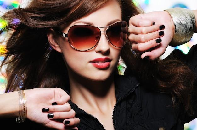 Mujer hermosa con estilo glamour con gafas de sol de moda y manicura negra
