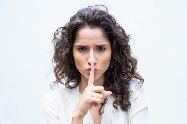Mujer hermosa estricta haciendo gesto shh