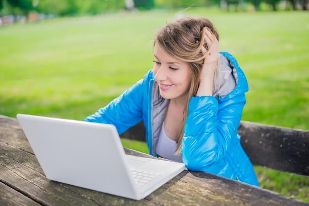 La mujer hermosa del estudiante está utilizando un ordenador portátil y que se sienta en un banco en el campus universitario. sonriente mujer está trabajando en un equipo al aire libre en el parque de la universidad. estudio al aire libre concepto.