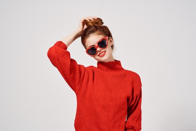 Mujer hermosa en un estudio de suéter rojo