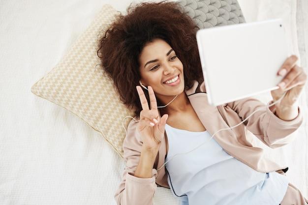 Mujer hermosa feliz en auriculares que sonríe mostrando la paz que hace el selfie en la tableta que miente en cama. desde arriba.