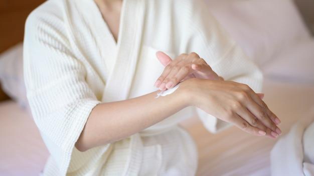 Una mujer hermosa feliz en bata de baño blanca aplicando crema hidratante corporal en el concepto de dormitorio, cuidado de la piel y tratamiento