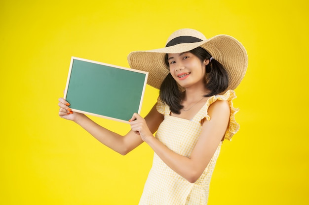 Una mujer hermosa y feliz con un gran sombrero y sosteniendo un tablero verde sobre un amarillo.
