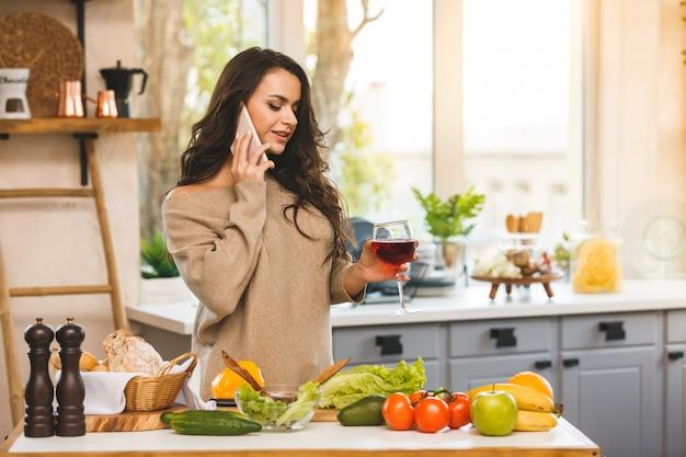 Mujer hermosa feliz que prepara la comida sana en la cocina mientras que habla en el teléfono.