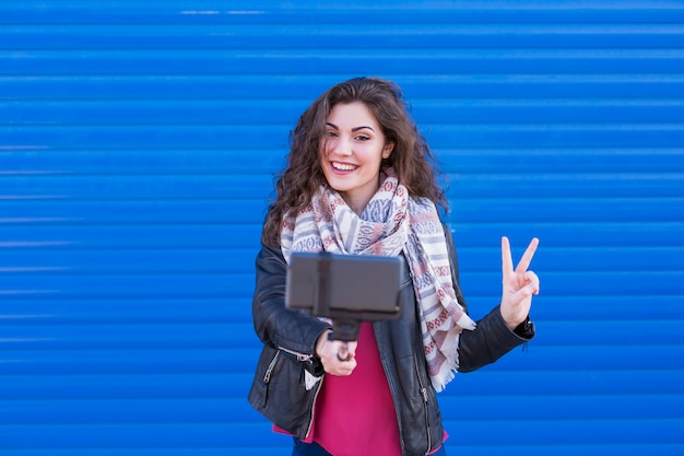 Mujer hermosa feliz que toma un selfie con el teléfono inteligente sobre fondo azul.